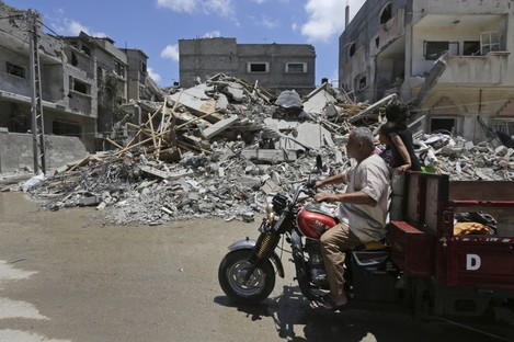 Palestinians drive by the rubble of a house destroyed by an overnight Israeli missile strike during the week-long conflict in Rafah, southern Gaza Strip.