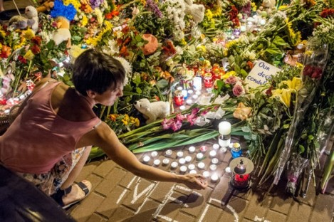A woman lights a candle outside the Embassy of the Netherlands in Kiev to commemorate victims of Malaysia Airlines Flight MH17.