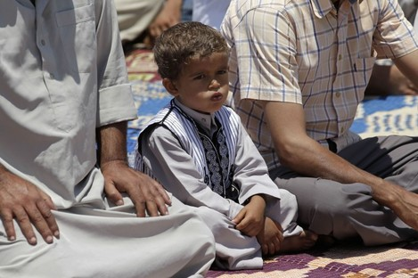 A Libyan child attends the Friday prayers with his father in Misrata today