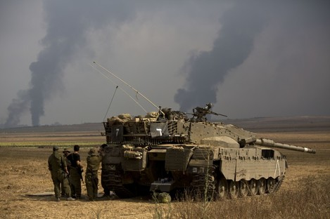 Israeli soldiers stand behind a tank as heavy smoke rises from the Gaza.