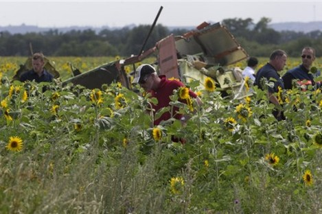 Dutch and Australian investigators examine pieces of the crashed Malaysia Airlines Flight 17 in the village of Rassipne, Donetsk region, eastern Ukraine today.