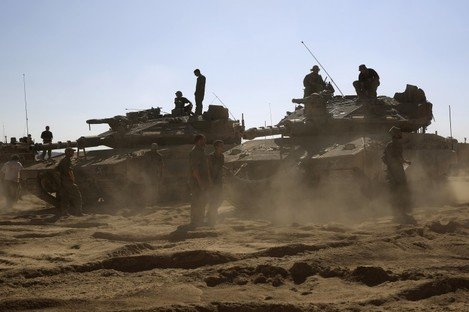 Israelis soldiers gather in a staging area near the Israel Gaza border yesterday.