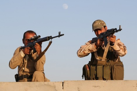 Kurdish Peshmerga fighters stand guard during airstrikes targeting Islamic State militants.