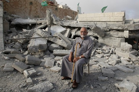 A Palestinian sits in the rubble of the house of Hussam Kawasma, one of three Palestinians identified by Israel as suspects in the killing of three Israeli teenagers, after it was demolished by the Israeli army in the West Bank city of Hebron yesterday.