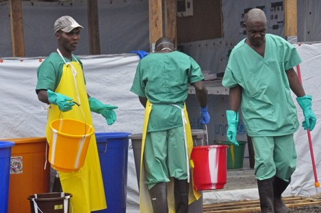 Health workers with buckets, as part of their Ebola virus prevention protective gear, at an Ebola treatment center in the city of Monrovia, Liberia.