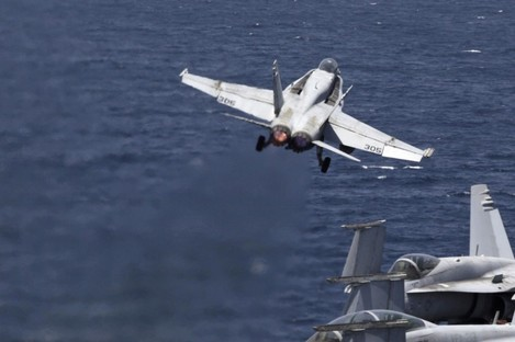 A U.S. F/A-18 fighter jet takes off for Iraq from the flight deck of the U.S. Navy aircraft carrier USS George H.W. Bush in the Persian Gulf.