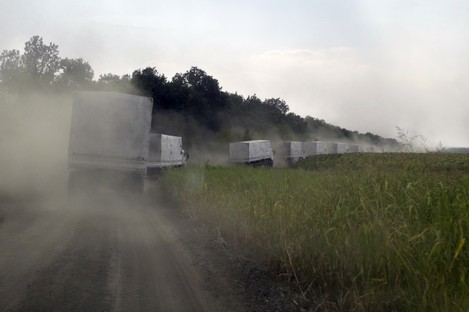 Russian aid convoy trucks roll along the main road to Luhansk .