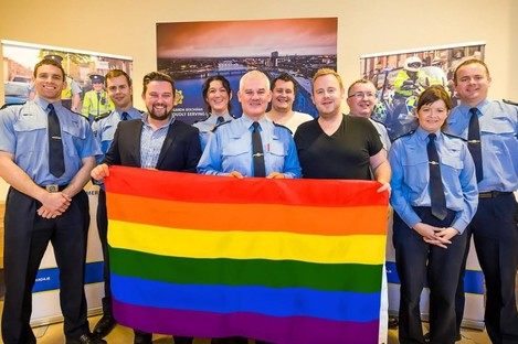 Gardaí at Henry Street station in Limerick smile while they stand behind a rainbow flag with Gay Pride organisers.
