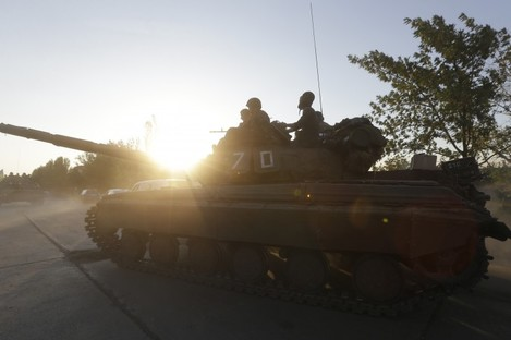 Members of the Ukrainian army ride on tanks in the port city of Mariupol on Friday.