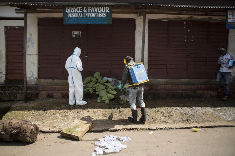 Health workers collect samples in an Ebola case in Sierra Leone