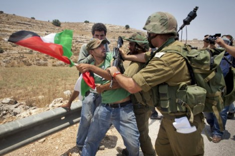 An unidentified protester holding a Palestinian flag scuffles with Israeli security forces during a joint pro-Palestinian demonstration held by foreign, Israeli and Palestinian demonstrators in the West Bank village of Nabi Saleh, Saturday, July 9, 2011.