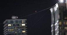 Man walks across tightrope between two skyscrapers - blindfolded
