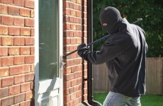 Four robbers burst into home where young children present, one woman injured