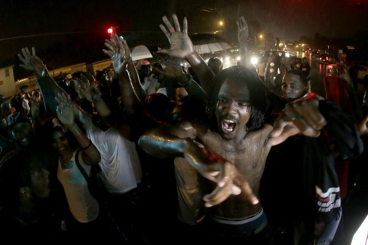 File photo. people defy a curfew before smoke and tear gas was fired to disperse a crowd protesting the shooting of teenager Michael Brown in Ferguson