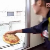 Lad throws a pizza into the oven from all the way across the street
