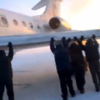 VIDEO: Passengers have to get out and push their airplane in the snow and ice