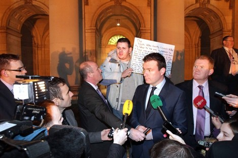 Alan Kelly is interrupted by a man holding a sign as he speaks to the media this evening.