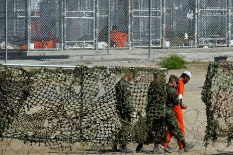 A detainee is escorted to interrogation by U.S. military guards at Camp X-Ray.