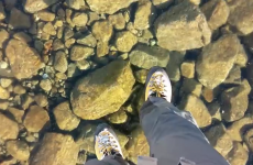 Watch two hikers walk out on an amazingly clear frozen lake