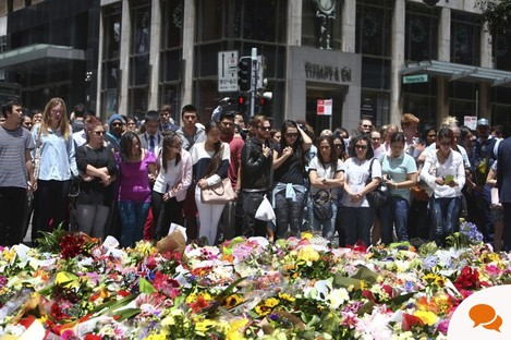 Staff members from the Lindt Chocolat Cafe with their arms linked pay tribute to their colleague who lost his live during a siege at the popular coffee shop at Martin Place in the central business district of Sydney, Australia, Tuesday, Dec. 16, 2014.