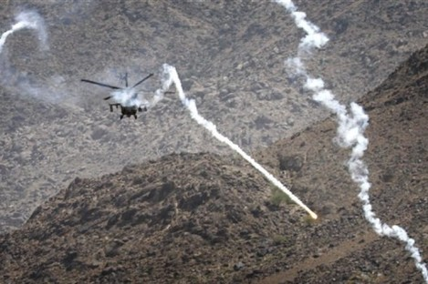 A coalition helicopter fires flares around a building, unseen, believed occupied by Taliban fighters in Kuz Kunar, Nangarhar province east of Kabul, Afghanistan, on Sunday 17 July