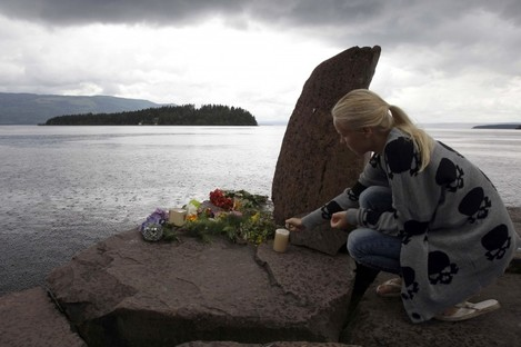 A girl lights a candle at a makeshift memorial opposite Utoya island