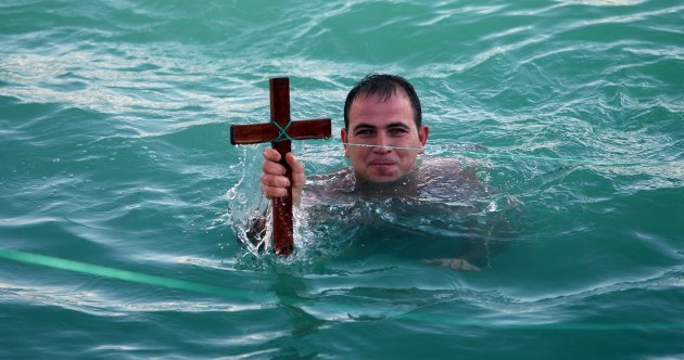 Orthodox Christians dive into ice-cold waters to chase wooden crosses