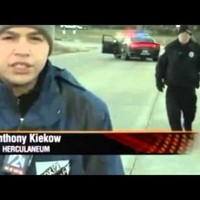 Cop has the uncoolest reaction ever when he realises he's in a live news shot