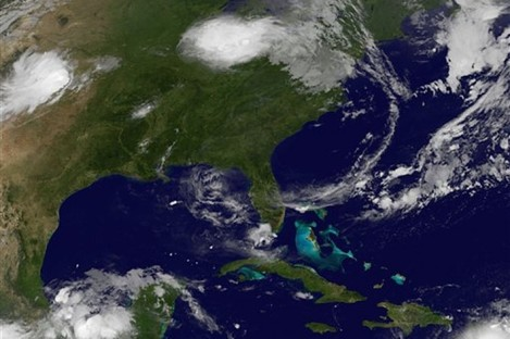 This image provided by NASA taken at 2:32 a.m. EDT Wednesday morning Aug. 3, 2011 shows tropical storm Emily, lower right.