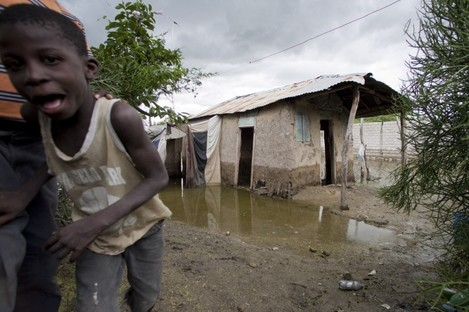 A boy looks at the camera as he walks past a partially flooded house on the outskirts of L'Estere, Haiti.