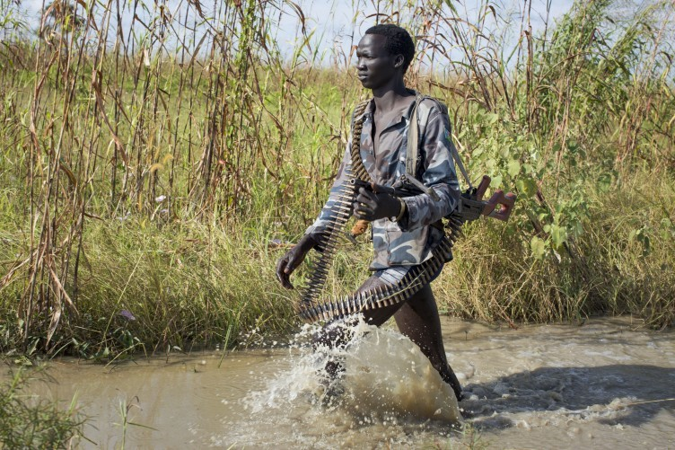 FILE: A rebel soldier patrols through a flooded area near the town of Bentiu, South Sudan