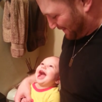 Baby boy gets almost too much joy from biting his dad's finger