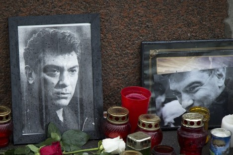 Flowers, votive candles and portraits are seen at the place where Boris Nemtso was gunned down