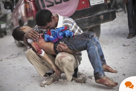A Syrian man cries while holding the body of his son, killed by the Syrian Army, near Dar El Shifa hospital in Aleppo, Syria in 2012.