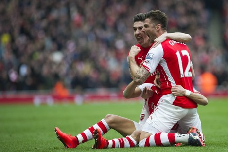 Arsenal's Alexis Sanchez, partially seen at bottom, celebrates with teammates Olivier Giroud, right, and Hector Bellerin.