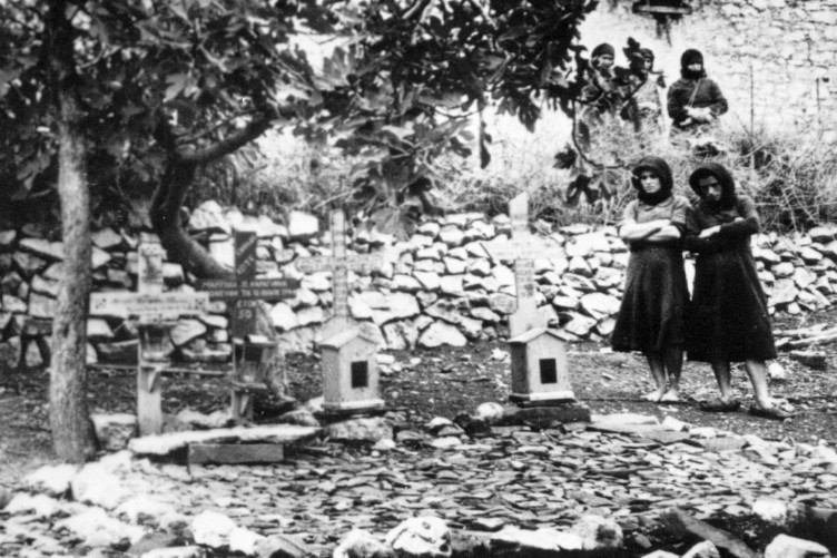 Women standing In the graveyard of Distomo, Greece, where victims of a 1944 Nazi massacre are buried