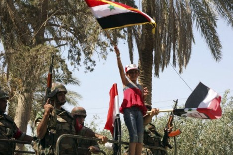 Image of a young girl carrying a Syrian flag as troops withdraw from Deir el-Zour earlier this week. The photo was taken during a Government organised media tour.