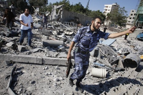 Hamas members check the damage to a Hamas training camp after an Israeli airstrike yesterday morning.