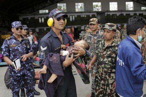 An Indian Air Force person carries a Nepalese child, wounded in earthquake, to a waiting ambulance after the child and mother were evacuated from a remote area at the airport in Kathmandu.