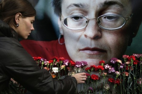 A woman places flowers at a memorial rally to Anna Politkovskaya in 2009