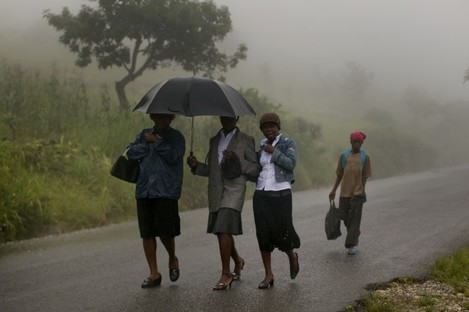 People in Haiti try to take shelter from the rain coming from Hurricane Irene. The hurricane is set to make landfall in the Bahamas and in the US in the next two days.