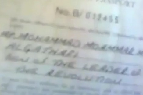 Still from a video which shows somebody flicking through the Libyan leader's diplomatic passport.