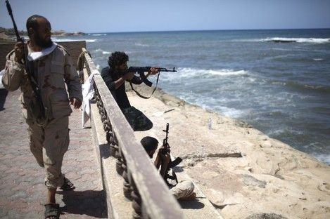 Rebel fighters fire on what is allegedly Gaddafi's beach house in Tripoli