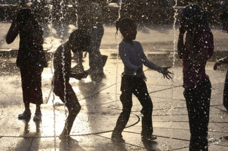 File photo: Iranian children play in a fountain during high temperatures last month.