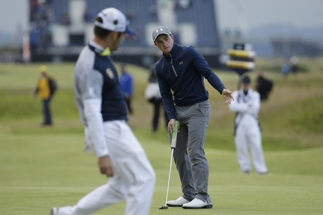 Dunne follows his putt on the 16th green as Ooosthuizen looks on.