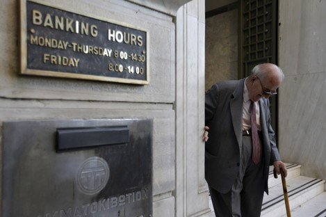 An elderly man leaves a branch of the National Bank of Greece in Athens.