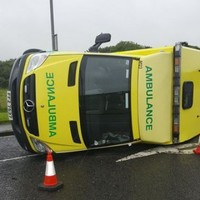 Ambulance with patient on board overturns after being hit from side
