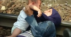 Pictures: Desperate mother clings to her baby as police try to bring migrants to camps