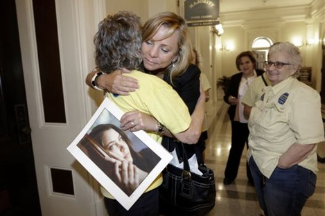 Debbie Ziegler holds a photo of her daughter, Brittany Maynard, as she receives congratulations from Ellen Pontac, after a right-to die measure was approved by the Assembly in Sacramento, California