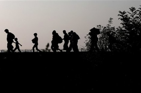 Migrants walk on the railway track after crossing the border line between Serbia and Hungary near Roszke, southern Hungary.